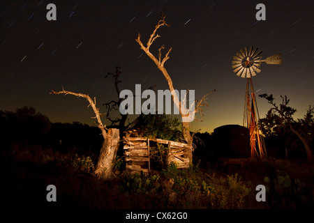 Star trails, old log cabin and windmill, Block Creek Natural Area, Texas - Stock Photo