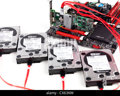 Closeup of four hard drives connected to computer motherboard with a RAID controller - Stock Photo