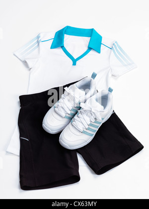 Womens sports outfit white shirt, black fitness shorts and running shoes isolated on white background - Stock Photo