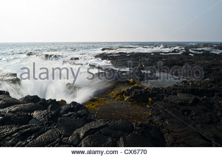 waves crashing on a rocky shore in Hawaii USA near Kona. - Stock Photo