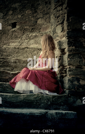 a woman in a red dress is sitting on stone steps - Stock Photo