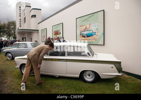 Visitor to Goodwood revival looking at Ford Lotus Cortina at the Motor Show display 2012 - Stock Photo