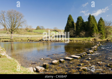 Two ways to cross the River Wharfe, across the bridge or on the stepping stones. Burnsall North Yorksire Dales England - Stock Photo