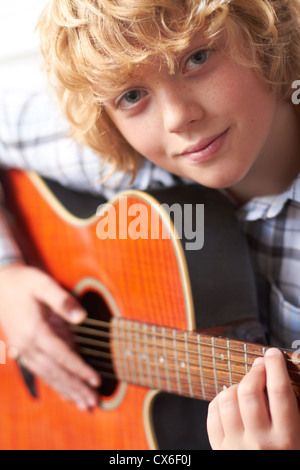 Boy learning To Play Acoustic Guitar - Stock Photo