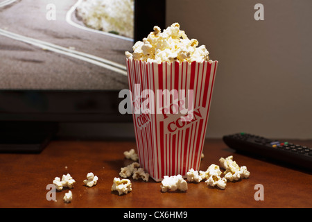 A red striped carton of popcorn on a table in front of a flat screen TV - Stock Photo