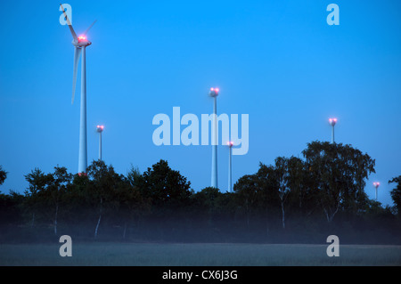 Windfarm at night consisting of German built Enercon E-40 turbines, one of which is under going maintenance and - Stock Photo