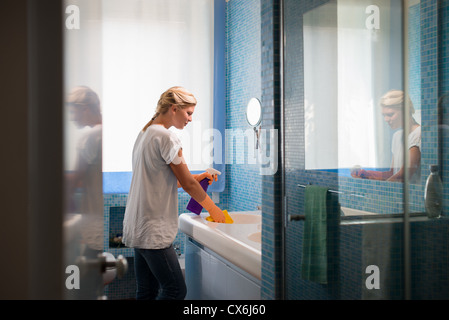 Housework and domestic lifestyle: woman doing chores in bathroom at home, cleaning wash basin and tap with spray - Stock Photo