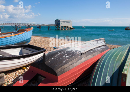 Boats on Selsey beach with lifeboat station in the background, West Sussex, UK. - Stock Photo