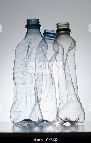 Three empty, partially crushed plastic water bottles - Stock Photo