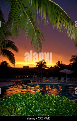 A tropical sunset lights up the sky and pool at the Hacienda Tres Rios Spa Resort, Playa Del Carmen, Riviera Maya, - Stock Photo