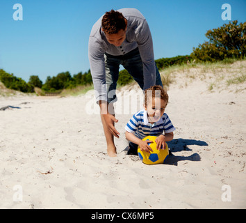 Excited kid grabs the ball as he plays a soccer game with his father - Stock Photo