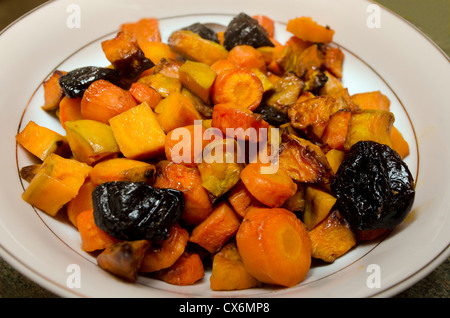 Roasted sweet vegetables and fruits (Carrot, sweet potato and pumpkin and prunes ) in bowl ready to be served. - Stock Photo