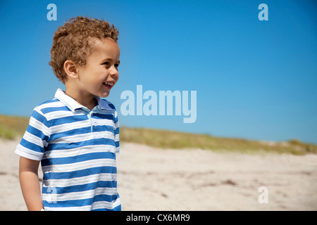 Adorable little boy enjoying the outdoors against the blue sky - Stock Photo