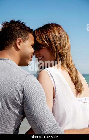 Couple looking at each other's eyes against blue background - Stock Photo