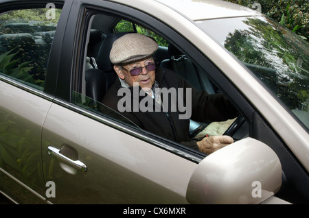 A very old man with a valid driving license drives his car. - Stock Photo