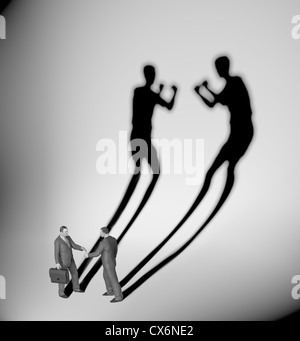 Two businessman casting a shadow shaped like two fighters - Stock Photo