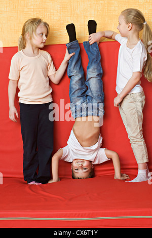 Two girls holding a boy upside down - Stock Photo