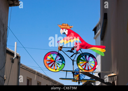 Colourful whirligig, parrot on the bicycle, house exterior decoration. - Stock Photo