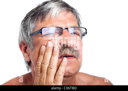 Close up of unhappy senior man with painful toothache, isolated on white background. - Stock Photo