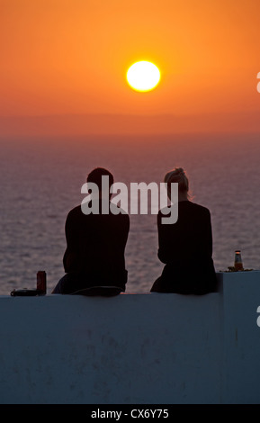 ALGARVE, PORTUGAL. A young couple silhouetted against the setting sun at Praia do Carvoeiro. 2012. - Stock Photo