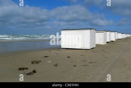 Bathing huts along the sandy beach at Blokhus in Jutland Denmark with waves breaking in the North Sea on a windy - Stock Photo