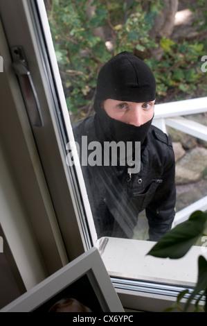 Burglar looking through house window - Stock Photo