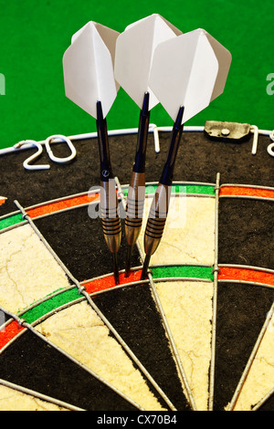 Three darts successfully scoring one hundred and eighty in a dartboard - Stock Photo