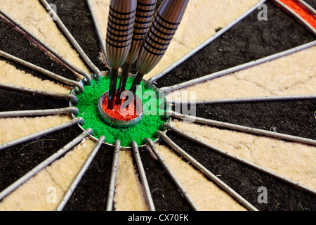 Three darts in the bullseye scoring one hundred and fifty in darts tournament - Stock Photo