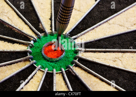 a dart hits target in the centre of a darts board good business concept for success - Stock Photo
