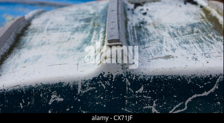 Faded and slightly damaged hull of an upturned rowing boat - Stock Photo
