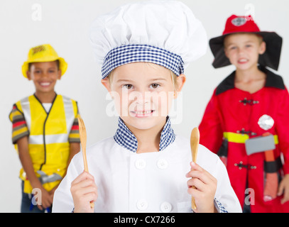 happy little chef in front of construction worker and fireman - Stock Photo