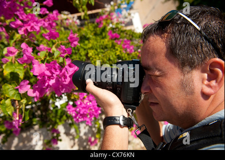 Close up of a photographer using a dslr camera to take a photograph. - Stock Photo