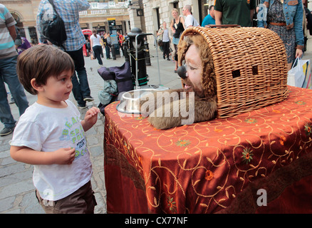 Child looking at a street human statue dressed as a dog in Convent Garden, central London - Stock Photo