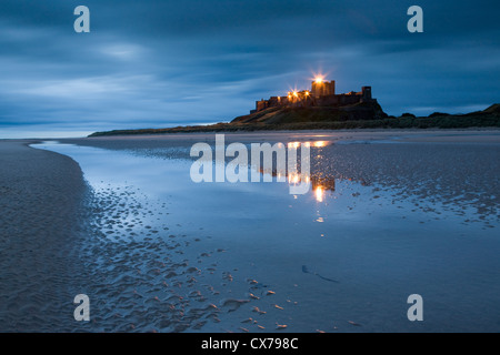 Bamburgh Castle on the Northumberland coast is reflected in water on the sandy deserted beach. - Stock Photo