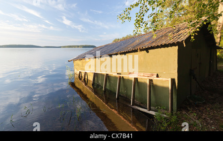Small green wooden boat garage on the coast of Saimaa lake, typically construction for Finland - Stock Photo
