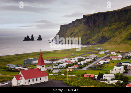 Aerial view over Vik (vik i myrdal) with its church and the reynisdrangar (basalt sea stacks) at dawn, South Iceland - Stock Photo