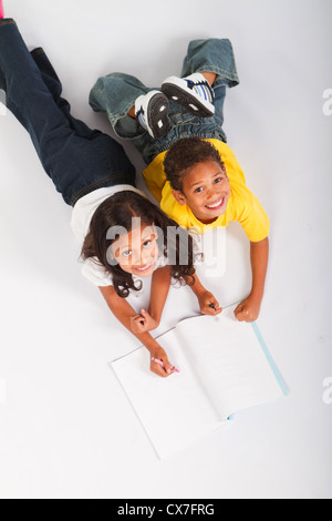 overhead view of two african american kids reading book - Stock Photo