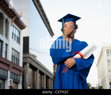 A Graduate In Cap And Gown Holds His Hand Over His Eyes; Victoria, British Columbia, Canada - Stock Photo