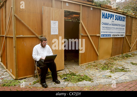 A man using a laptop computer outside the sukkot in Washington Square Park - Stock Photo