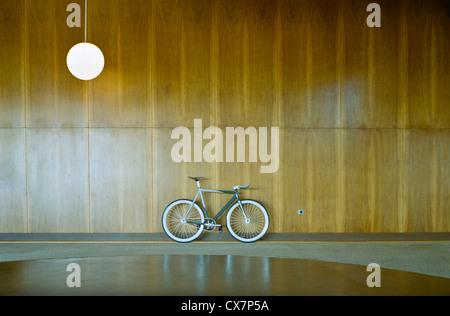 Bike parked against wood paneling - Stock Photo