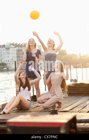 Four female friends tossing a ball around on a jetty next to Spree River, Berlin, Germany - Stock Photo