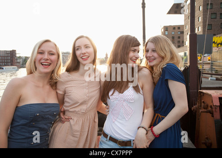 Four female friends standing side by side, Spree River, Berlin, Germany - Stock Photo