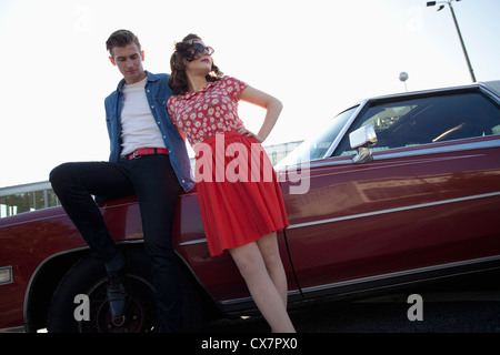 A cool, rockabilly couple leaning against a vintage car - Stock Photo