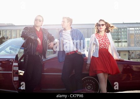 Three rockabilly friends leaning against a vintage car - Stock Photo