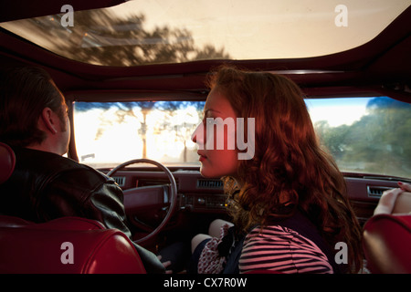 A rockabilly couple in the front seat of a vintage car - Stock Photo