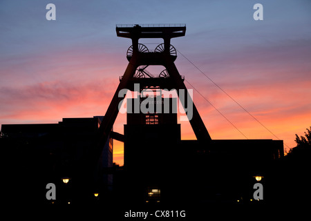 colourful sunset at the winding tower of shaft 12 at Zollverein Coal Mine Industrial Complex in Essen, Germany - Stock Photo