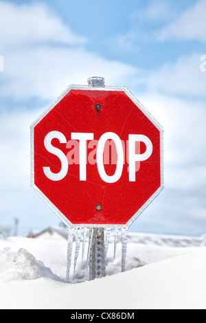 A stop sign with icicles hanging from in while almost buried in a deep snow bank. - Stock Photo