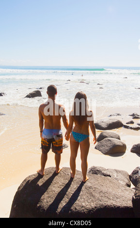 A couple stand holding hands on a large rock looking out at the ocean;Green mount coolangatta gold coast queensland - Stock Photo