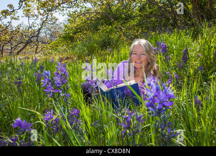 A Senior Woman Reads In A Sea Of Camassia; Victoria British Columbia Canada - Stock Photo