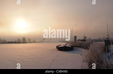 Sunrise in winter over a frozen canal and windmills at the famous dutch UNESCO site Kinderdijk, Holland. - Stock Photo
